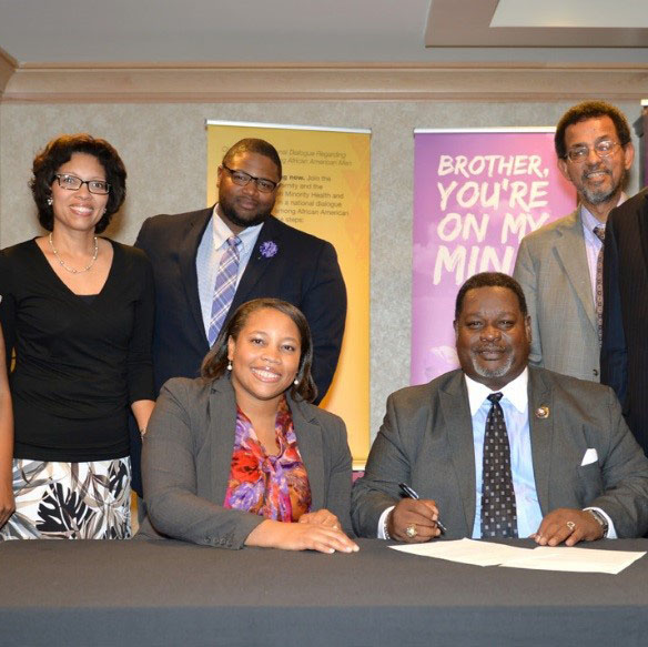 On hand at the signing of the BYOMM agreement are (seated) Dr. Courtney Ferrell Aklin of NIMHD and Antonio F. Knox, Sr. of Omega Psi Phi.