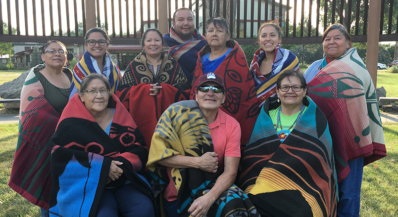 10 people wrapped in Native American blankets pose for a photograph outside.